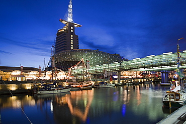 Night view of climate house at old port with moored boats in Bremerhaven, Bremen, Germany