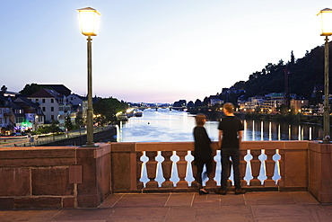 Couple standing on Karl-Theodor Bridge overlooking Neckar at dusk in Heidelberg, Germany