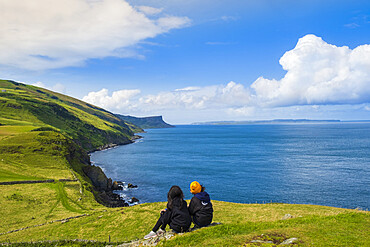 Two young hikers taking a rest on a walking trail along the Antrim coast, Ulster, Northern Ireland, United Kingdom, Europe