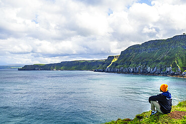 A young hiker taking a rest on a walking trail along the Antrim coast, Ulster, Northern Ireland, United Kingdom, Europe