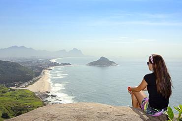 A young hiker looking out from the viewpoint over Pontal and Recreio dos Bandeirantes beaches in Barra da Tijuca, Rio de Janeiro, Brazil, South America