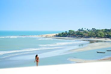 A young woman walking along the beach in Jericoacoara, Ceara, Brazil, South America