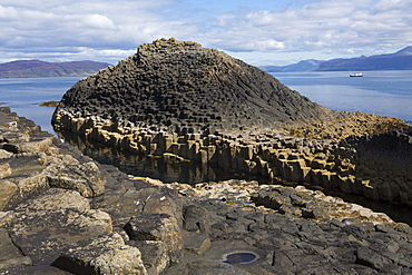 Basalt columns next to Fingal's Cave on the Isle of Staffa, with Mull in the background, Inner Hebrides, Scotland, United Kingdom, Europe