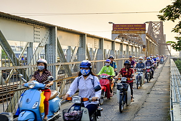 Motorbike commuters on a pedestrian pavement (sidewalk) on a railway bridge over the Red River in Hanoi, Vietnam, Indochina, Southeast Asia, Asia