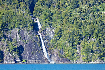 A boat in front of a waterfall on Puelo Lake in the Tagua Tagua reserve, Patagonia, Chile, South America