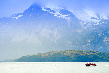 Dingy in a fjord in Alberto de Agostini National Park with the Darwin mountain range (Cordillera Darwin) behind, Patagonia, Chile, South America