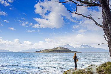 Woman looking out over the Magellan Straits and Darwin Mountain range in Tierra del Fuego National Park, Argentina, South America