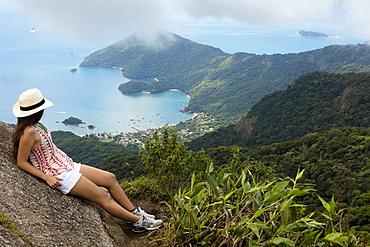 Young woman looking out over the Green Coast (Costa Verde) from Papapagaio peak (Pico do Papagaio) on Ilha Grande island, Rio de Janeiro state, Brazil, South America