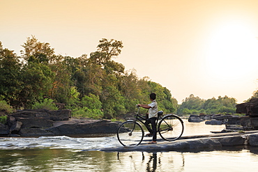 School boy on a bicycle crossing a river on his way to school, Chi Phat, Koh Kong, Cambodia, Indochina, Southeast Asia, Asia