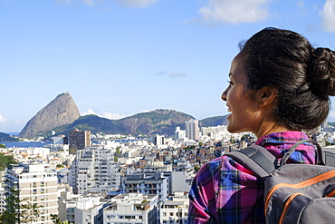 Young backpacker on her mobile phone in central Rio de Janeiro with the Sugar Loaf in the distance, Rio de Janeiro, Brazil, South America