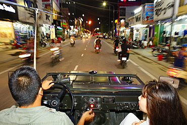 A Vietnamese couple in an open-top Jeep driving through the streets of Hue, Vietnam, Indochina, Southeast Asia, Asia