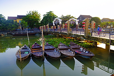 Boats on the Thu Bon River with a cyclist on the Lantern Bridge in Hoi An, UNESCO World Heritage Site, Quang Nam, Vietnam, Indochina, Southeast Asia, Asia