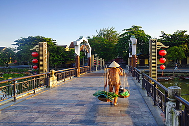 A woman carrying baskets on a yoke over the Lantern Bridge in Hoi An, Quang Nam, Vietnam, Indochina, Southeast Asia, Asia