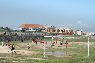 Children playing football outside the Spanish colonial city walls of Cartagena in the Colombian Caribbean, Cartagena, Colombia, South America