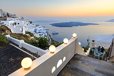 The fiery red sky on the Aegean Sea after sunset seen from the typical terraces of Firostefani, Santorini, Cyclades, Greek Islands, Greece, Europe