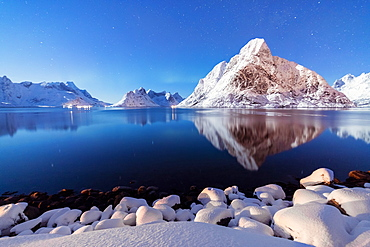 The snowy peaks are reflected in the frozen sea on a starry winter night, Reine Bay, Nordland, Lofoten Islands, Arctic, Norway, Scandinavia, Europe