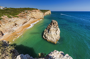 The turquoise waters of the ocean frames the sandy beach of Praia do Torrado, Algarve, Lagoa, Faro District, Portugal, Europe