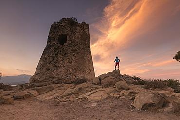 Hiker admires sunset from the stone tower overlooking the bay, Porto Giunco, Villasimius, Cagliari, Sardinia, Italy, Mediterranean, Europe
