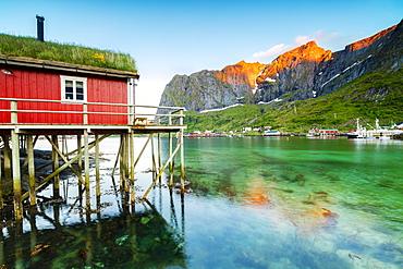 Typical house of fishermen called Rorbu lit up by midnight sun, Reine, Nordland county, Lofoten Islands, Arctic, Northern Norway, Scandinavia, Europe