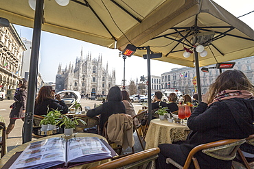 Tourists in the cafe contemplate the Duomo and its square, Milan, Lombardy, Italy, Europe