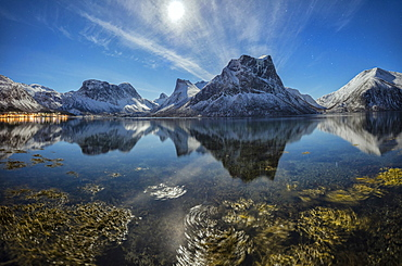 Panorama of snowy peaks reflected in sea in a cold starry night, Bergsbotn, Senja, Troms County, Norway, Scandinavia, Europe