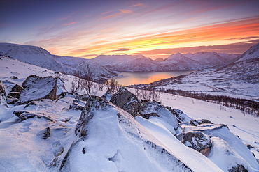 Frozen sea surrounded by snow framed by the orange sky at sunset, Torsken, Senja, Troms County, Arctic, Norway, Scandinavia, Europe