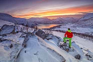 Hiker admires the frozen sea surrounded by snow framed by the orange sky at sunset, Torsken, Senja, Troms County, Arctic, Norway, Scandinavia, Europe