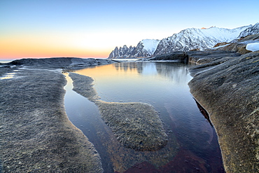 Orange sky at sunset reflected on snowy peaks and the frozen sea surrounded by rocks Tungeneset, Senja, Troms County, Arctic, Norway, Scandinavia, Europe
