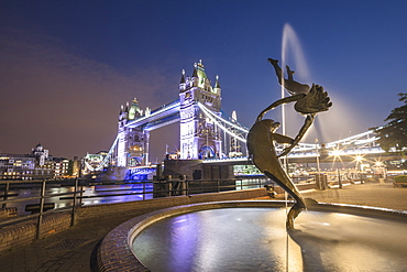 The Girl With A Dolphin Fountain frames Tower Bridge reflected in the River Thames at night, London, England, United Kingdom, Europe