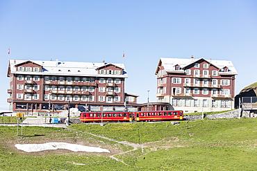 Red wagons of Wengernalpbahn rack railway run next to alpine hotels, Wengen, Bernese Oberland, Canton of Bern, Switzerland, Europe