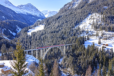 Red train of Rhaetian Railway on Langwieser Viaduct surrounded by snowy woods, Canton of Graubunden, Switzerland, Europe