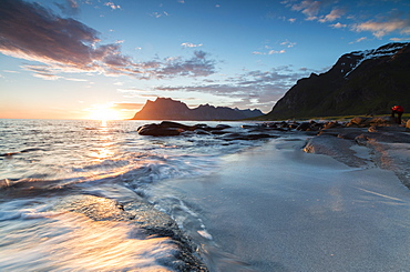 Pink clouds and midnight sun reflected on the waves of blue sea framed by rocky peaks, Uttakleiv, Lofoten Islands, Norway, Scandinavia, Europe