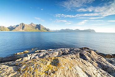 Sun shines on the blue sea and the rocky peaks at night during summer, Vikten, Nord Trondelag, Lofoten, Norway, Scandinavia, Europe