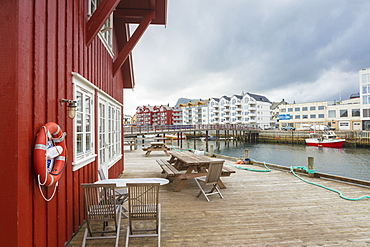 Clouds frame the typical wooden houses of the fishing village surrounded by sea, Svolvaer, Vagan, Lofoten Islands, Norway, Scandinavia, Europe