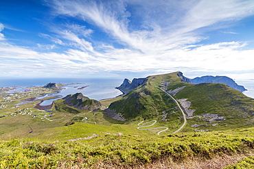 Steep road of curves in between green meadows and sea, Sorland, Vaeroy Island, county of Nordland, Lofoten Islands, Norway, Scandinavia, Europe