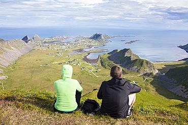 Couple on top of peak admire sea framing the village of Sorland, Vaeroy Island, Nordland county, Lofoten archipelago, Norway, Scandinavia, Europe