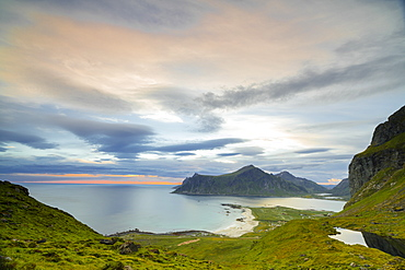 Pink clouds of the midnight sun reflected in the cold sea, Flakstad, Moskenesoya, Nordland county, Lofoten Islands, Norway, Scandinavia, Europe