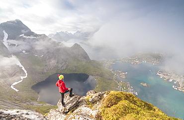 Hiker on summit admires the blue lake and sea framing the village, Reinebringen, Moskenesoya, Lofoten Islands, Norway, Scandinavia, Europe