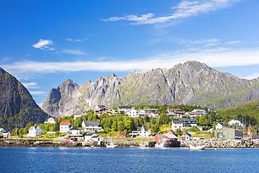 The blue sea frames the fishing village and the rocky peaks, Reine, Moskenesoya, Lofoten Islands, Norway, Scandinavia, Europe