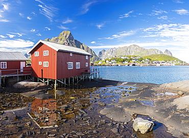 Typical house of fishermen called Rorbu reflected in blue sea, Reine, Moskenesoya, Lofoten Islands, Norway, Scandinavia, Europe