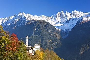 The colorful trees frame the alpine church and the snowy peaks, Soglio, Bregaglia Valley, Canton of Graubunden, Swiss Alps, Switzerland Europe
