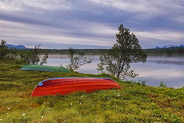 Boats on green meadows frame the calm water at night, Bogen, Evenes, Ofotfjorden, Nordland, Norway, Scandinavia, Europe