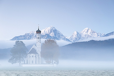 The autumn fog at sunrise frames St. Coloman Church surrounded by snowy peaks, Schwangau, Bavaria, Germany, Europe