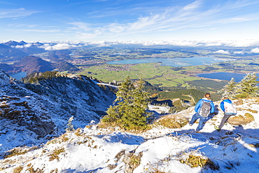 Hikers on steep crest covered with snow in the Ammergau Alps, Tegelberg, Fussen, Bavaria, Germany, Europe