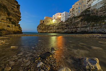 Dusk lights on the clear sea framed by the old town perched on the rocks, Polignano a Mare, Province of Bari, Apulia, Italy, Europe