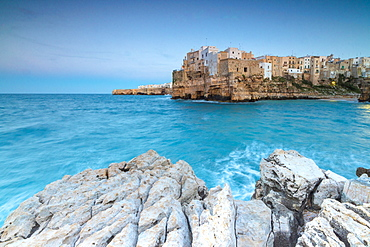 Turquoise sea at dusk framed by the old town perched on the rocks, Polignano a Mare, Province of Bari, Apulia, Italy, Europe