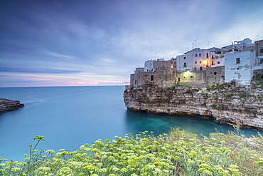 Turquoise sea at sunrise framed by the old town perched on the rocks, Polignano a Mare, Province of Bari, Apulia, Italy, Europe