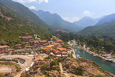 The typical village and harbor of Porto immersed in the green vegetation of the promontory, Southern Corsica, France, Mediterranean, Europe