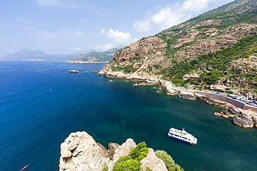 Tourist boat in the turquoise sea framed by limestone cliffs, Porto, Southern Corsica, France, Mediterranean, Europe