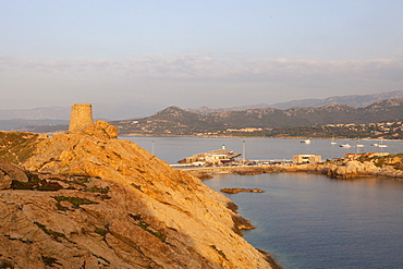 The ancient Genoese tower overlooking the blue sea surrounding the village of Ile Rousse, Balagne Region, Corsica, France, Mediterranean, Europe